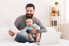 Businessman reading documents and sitting with baby royalty free stock image