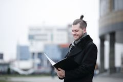 Businessman reading documents standing on a city street. stock photos