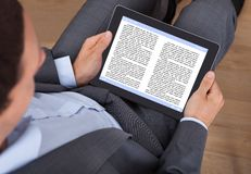 Businessman reading ebook in office Royalty Free Stock Photography