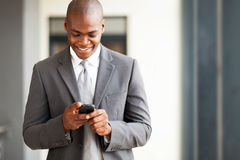 Businessman reading email. Young african american businessman reading email on smart phone Stock Photography