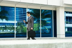 Businessman Reading Email On Mobile Phone Walking To Office Royalty Free Stock Image