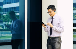 Businessman Reading Email On Mobile Phone Walking To Office Royalty Free Stock Photo
