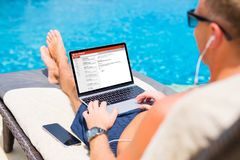 Businessman reading email by the pool stock images