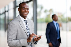 Businessman reading email. Smiling young african businessman reading email on smart phone royalty free stock images