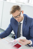 Businessman reading file at desk in creative office Royalty Free Stock Photography