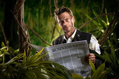 Businessman reading financial news in the jungle Stock Image
