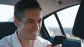 Businessman reading a good message on the smartphone, he is happy and smiling. Man rides a car with a driver or taxi and stock video