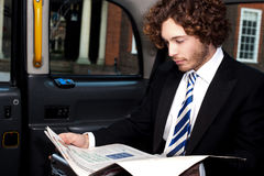Businessman reading magazine inside taxi Royalty Free Stock Images