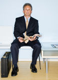Businessman reading magazine in waiting room Stock Image