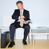 Businessman reading magazine in waiting room Stock Photography