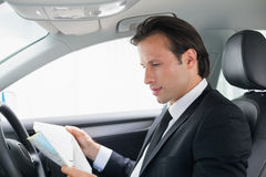 Businessman reading a map Stock Images