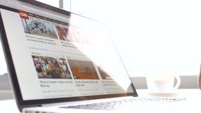 Businessman reading news cnn on a laptop in an office building. Man  reading news cnn on a laptop in an office building stock video