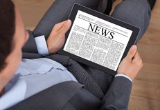 Businessman reading news on digital tablet in office Royalty Free Stock Photos