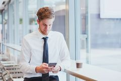 Businessman reading news and emails on his smartphone. In modern interior stock photos