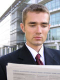 Businessman reading newspaper. Outdoors Stock Photo