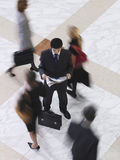 Businessman Reading Newspaper Amid Blurred Walking People Royalty Free Stock Images