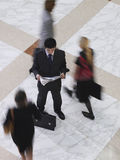 Businessman Reading Newspaper Amid Blurred Walking People Royalty Free Stock Photos