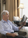 Businessman Reading Newspaper In Armchair. Side view of a smiling middle aged businessman sitting in armchair reading newspaper Stock Photo