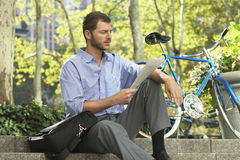 Businessman Reading Newspaper By Bicycle. Young businessman reading newspaper by bicycle in park royalty free stock photography