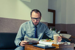 Businessman reading newspaper during breakfast at home/hotel. In. Door photo Stock Photos