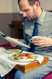 Businessman reading newspaper during breakfast at home/hotel. In. Door photo Stock Image