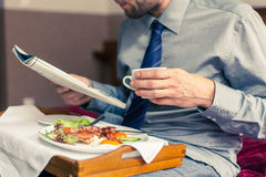 Businessman reading newspaper during breakfast at home/hotel. In. Door photo Royalty Free Stock Images