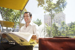 Businessman Reading Newspaper At Bus Stop Stock Image