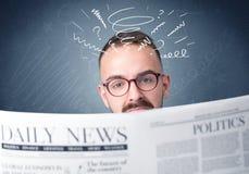 Businessman reading newspaper. Confused businessman holding and reading newspaper Stock Photo