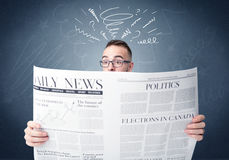 Businessman reading newspaper. Confused businessman holding and reading newspaper Stock Images