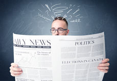Businessman reading newspaper. Confused businessman holding white newspaper Stock Photography