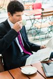 Businessman reading a newspaper and drinking coffee in the morni stock photos