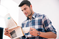 Businessman reading newspaper and drinking coffee in office Stock Photos