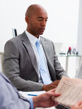 Businessman reading a newspaper in the foreground Stock Image