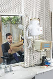 Businessman Reading Newspaper In Hair Salon Royalty Free Stock Photo
