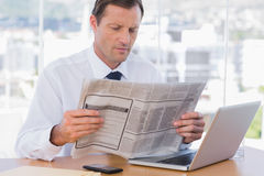 Businessman reading a newspaper Stock Photos