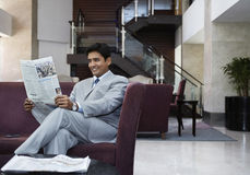 Businessman Reading Newspaper In Hotel Lobby Stock Photography