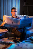 Businessman reading newspaper late at night Royalty Free Stock Photo