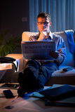 Businessman reading newspaper late at night Royalty Free Stock Photos