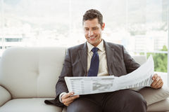 Businessman reading newspaper in living room Royalty Free Stock Photography