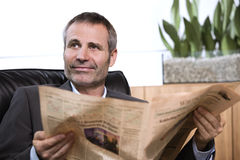 Businessman reading newspaper and looking up. Stock Photo