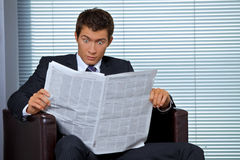 Businessman reading newspaper in office Royalty Free Stock Photos