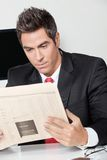 Businessman Reading Newspaper In Office Stock Photography