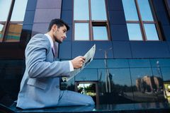 Businessman reading newspaper outdoors Stock Photos