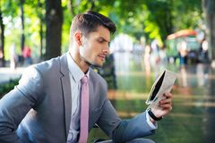 Businessman reading newspaper outdoors Stock Image