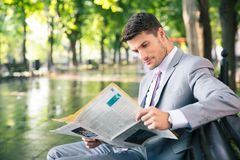 Businessman reading newspaper outdoors Stock Images