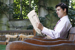 Businessman Reading Newspaper On Park Bench Royalty Free Stock Photos