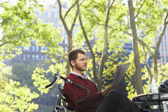 Businessman Reading Newspaper In Park. Young businessman reading newspaper in park royalty free stock image