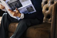 A businessman reading newspaper sitting on couch royalty free stock photography