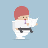 Businessman reading a newspaper in the toilet Stock Images