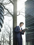 Businessman Reading Newspaper Under Tree Royalty Free Stock Photos